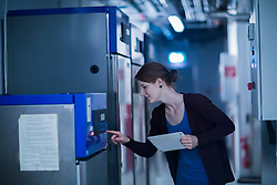 Young female engineer using a digital tablet and controlling a switchgear in control room, Freiburg im Breisgau, Baden-Wuerttemberg, Germany
