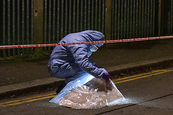 © Licensed to London News Pictures. 20/01/2020. London, UK. A forensic investigator looks under an evidence bag covering an unknown item. Police cordoned off a road & park and searched a property approximately half a mile from the location where an investigation was launched into the deaths of three men in Redbridge, all of whom had suffered apparent stab injuries.. Photo credit: Peter Manning/LNP