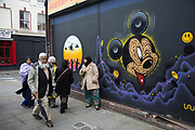 Muslims walk past a Mickey Mouse work. Street art near Brick Lane in the East End of London. This is an ever changing visual enigma, as the artworks constantly change, as councils clean some walls or new works go up in place of others. While some consider this vandalism or graffiti, these artworks are very popular among local people and visitors alike, as a sense of poignancy remains in the work, many of which have subtle messages.