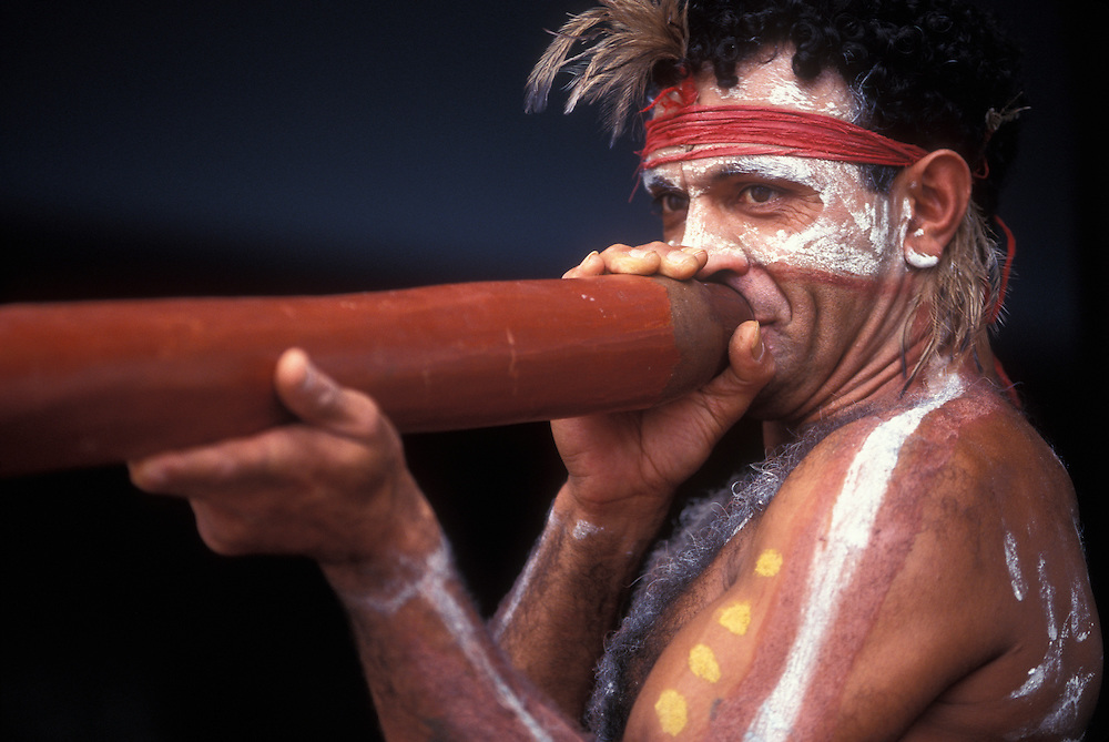 Australia, NSW, (MR) David Kennedy, wearing traditional Aboriginal face and body paints, plays the dijeradoo in Sydney
