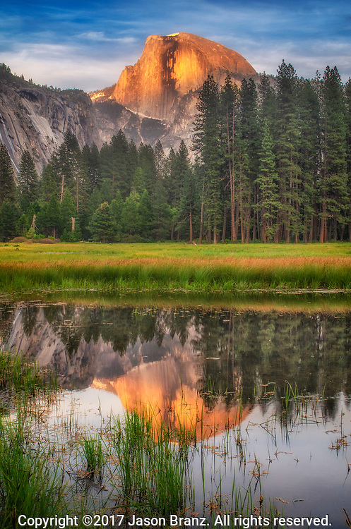 Half Dome at sunset reflected in a snowmelt pool on Cook's Meadow, Yosemite National Park, California.