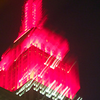 The Empire State building bursting in glistening red and white against a moonless night.