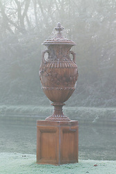 Terracotta urn with cobwebs in fog and frost