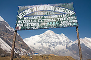 A sign welcomes trekkers to Annapurna Base Camp, the end goal of the Annapurna Sanctuary trek, in the Himalaya Mountains, Nepal. Annapurna South rises in the distance.