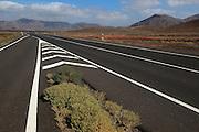 Chevron road lines on main highway through  Malpaís Grande national park, Fuerteventura, Canary Islands, Spain