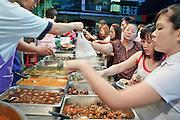 Mar. 24, 2009 -- BANGKOK, THAILAND: Thais get their dinner on a street side food cart in Bangkok. Bangkok is famous for its street cuisine. Photo by Jack Kurtz
