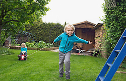 Older brother pulling sister on toy car in garden