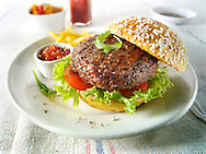 Char grilled beef burger  with chips and salad and a seseme bun photo. Funky Stock Photos