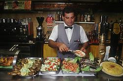 Barman serving behind tapas bar with display of prawns; sardines; tortilla and salad,