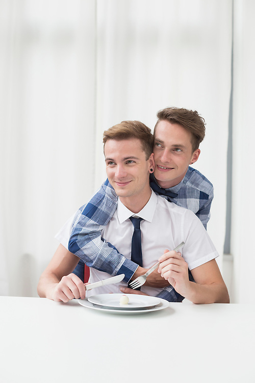 Homosexual couple with chocolate truffle on plate, smiling