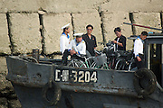 """North Korean sailors on a boat in the river port town of Sinuiju July 8, 2006. China and North Korea are separated by the Yalu River, upon which Chinese tourists take pleaure cruises across the water to observe their less economically developed neighbors.  North Korea has threatened to take """"stronger physical actions"""" after Japan imposed punitive measures in response to its barrage of missile tests and pushed for international sanctions. North Korea has vowed to carry out more launches and has said it will use force if the international community tries to stop it. DPRK, north korea, china, dandong, border, liaoning, democratic, people's, rebiblic, of, korea, nuclear, test, rice, japan, arms, race, weapons, stalinist, communist, kin jong il"""