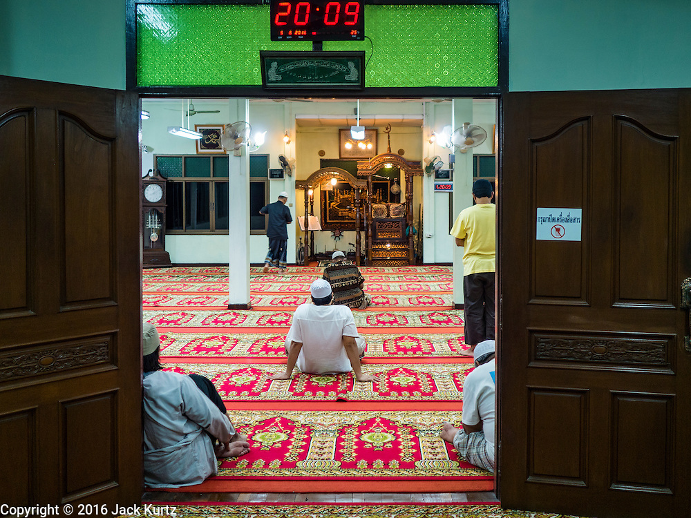 05 JUNE 2016 - BANGKOK, THAILAND:  Men wait for evening prayers to start in the prayer room at Masjid Darul Faha, a small mosque in the Muslim majority neighborhood of Ban Krua in Bangkok on the night before the start of Ramadan. Ramadan is the ninth month of the Islamic calendar, and starts on June 6 this year. It is observed by Muslims worldwide as a month of fasting to commemorate the first revelation of the Quran to Muhammad according to Islamic belief. This annual observance is regarded as one of the Five Pillars of Islam. Islam is the second largest religion in Thailand.      PHOTO BY JACK KURTZ