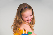 excited and happy Young girl of three plays with colourful building blocks