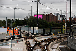 © Licensed to London News Pictures. 27/07/2019. Manchester, UK. British Prime Minister BORIS JOHNSON (in crowd of people wearing orange high visibility vests) visits an under construction area of the Trafford Line extension by Manchester's Pomona Metrolink tram stop during a visit to the city . Johnson will re-announce the HS3 rail link between Manchester and Leeds at a speech in Manchester City Centre today . Photo credit: Joel Goodman/LNP