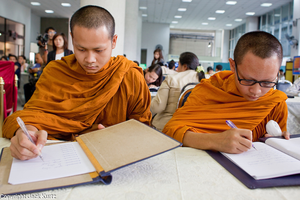 Sept. 22, 2009 -- BANGKOK, THAILAND:  Buddhist monks sign get well notes in the lobby of Siriraj Hospital for King Bhumibol Adulyadej, the 81-year-old King of Thailand. The King, a former monk himself, has been admitted to hospital suffering from a fever. Doctors at Siriraj Hospital said the world's longest-serving monarch, had shown signs of fatigue and was being treated with antibiotics. King Bhumibol is deeply revered by most Thais and his health is a matter of public anxiety. His Majesty was admitted on Saturday suffering from a fever, fatigue and loss of appetite. Doctors continued to treat the King with intravenous drips and antibiotics, hospital officials said. More than 3,500 people have come to the hospital to pray for the King's speedy recovery and to sign get well cards for him.  Photo by Jack Kurtz
