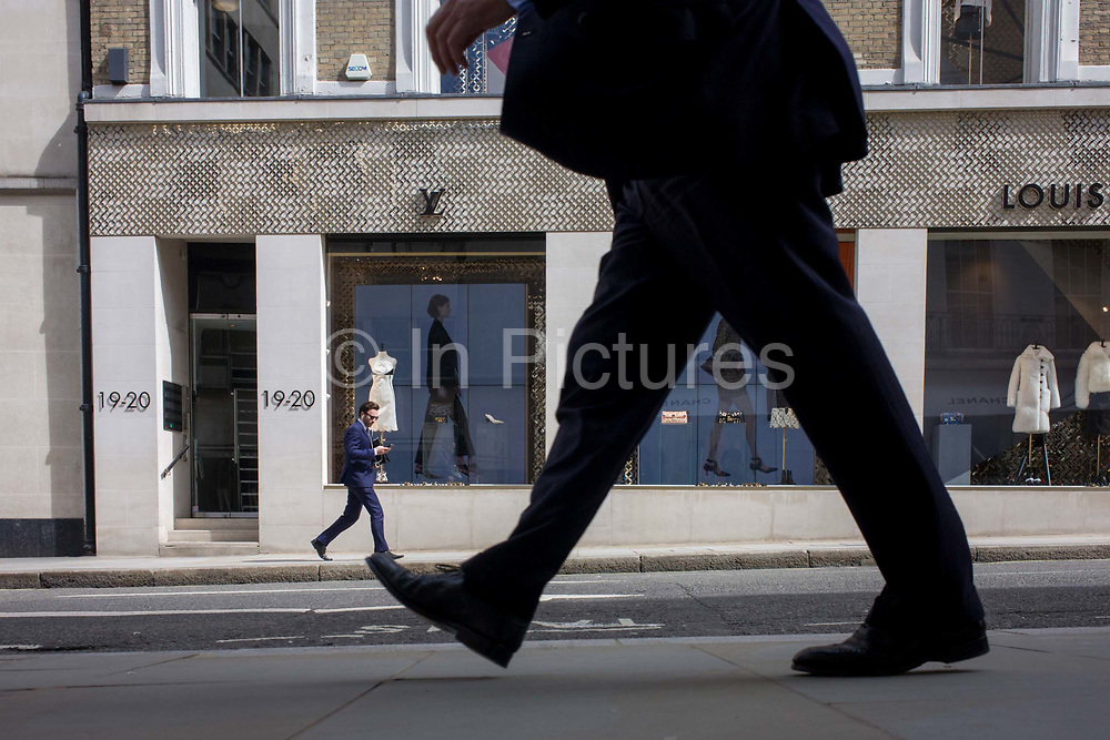 A walking theme shop window display at Louis Vuitton on Bond Street, central London. We look at ground level, through the legs of the passing person whose stride indicates a fast pace. A foot is about to be placed on the pavement while in the background another man makes his way along the street. They are alongside two video screens showing a loop of models on the catwalk, each also seen walking in profile, the same as the shoppers and workers. The location is 19-20 Bond Street, a street in the West End of London, connecting Piccadilly in the south to Oxford Street in the north. The street, consisting of two sections, has been a popular shopping area since the 18th century and is the home of many fashion outlets that sell prestigious and expensive items.