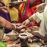 Naal Taanna (Braiding of the pure thread, the Saatnaala) is a Marwari pre-wedding ceremony where a thread is looped around the toes to make a thick band which is then tied onto the groom's and the bride's wrist by their respective families. The thread is tied with seven knots. Once the wedding is over, the bride and groom have to open each other's seven knots using only one hand for the job. This game helps break the ice between the traditionally-recently-met newlyweds. <br /> Udaipur, Rajasthan, 2011