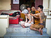 "07 MARCH 2015 - NAKHON CHAI SI, NAKHON PATHOM, THAILAND:  A man gets a ""sak yant"" tattoo at the Wat Bang Phra tattoo festival. Wat Bang Phra is the best known ""Sak Yant"" tattoo temple in Thailand. It's located in Nakhon Pathom province, about 40 miles from Bangkok. The tattoos are given with hollow stainless steel needles and are thought to possess magical powers of protection. The tattoos, which are given by Buddhist monks, are popular with soldiers, policeman and gangsters, people who generally live in harm's way. The tattoo must be activated to remain powerful and the annual Wai Khru Ceremony (tattoo festival) at the temple draws thousands of devotees who come to the temple to activate or renew the tattoos. People go into trance like states and then assume the personality of their tattoo, so people with tiger tattoos assume the personality of a tiger, people with monkey tattoos take on the personality of a monkey and so on. In recent years the tattoo festival has become popular with tourists who make the trip to Nakorn Pathom province to see a side of ""exotic"" Thailand.  PHOTO BY JACK KURTZ"