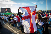 An England fans gets their flag ready for the Euro 2020 semi final match between England and Denmark on the 7th of July 2021 at the outdoor screen at Folkestone Harbour Arm, in Folkestone, United Kingdom.
