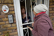 Save Cressingham Gardens campaigner Malika Belarabi talks with Mary Parker at her front door on 3rd February 2015 in South London, United Kingdom. Cressingham Gardens is a council garden estate, located on the southern edge of Brockwell Park. It comprises of 306 dwellings and built to the design of Lambeth Borough Council architect Edward Hollamby in the early 1970s. In 2012, Lambeth Council proposed regeneration of the estate, a decision highly opposed by many residents. Since the announcement, the highly motivated campaign group Save Cressingham Gardens has been active.