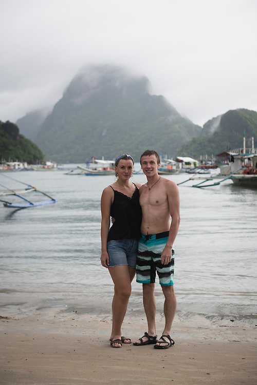 El Nido, Palawan, Philippines - July 14, 2019: A Russian couple on their honeymoon photographed at the end of a day-long boat trip to various islands and beaches around El Nido.