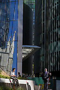 Londoners enjoy the sunshine with the reflection of the church of St. Mary Axe and financial services offices in the City of London, the capital's historic financial district, on 2nd August 2018, in London, England.