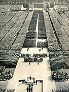 Staged Nuremberg Rally of Nazi Party members addressed by Hitler (foreground)