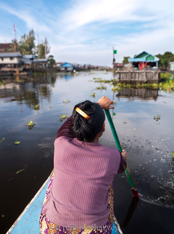A woman paddles her boat through the floating village of Kompong Phluk on the great Tonlé Sap lake, Cambodia