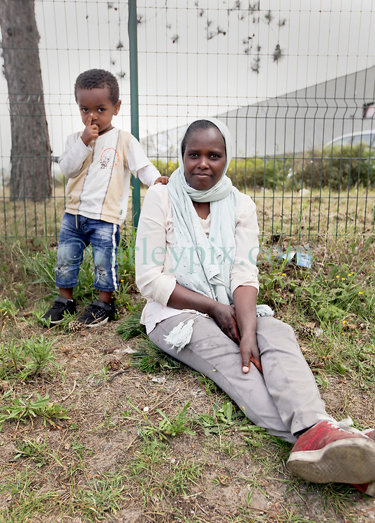 26 June 2020. Zone des Dunes, refugee camp, Calais, France.<br /> A young refugee mother sits at the side of the road with her young 2 year old son close to the tented refugee camp at Zone des Dunes in Calais, a relatively new refugee camp which sprang up just outside the notorious 'Jungle' camp which was closed down by authorities. The mother who did not wish to be named is a refugee from war torn Eritrea. She made her way overland from Eritrea to Sudan and from Sudan through what she described as extremely dangerous Libya. From Libya she was able to get on a boat to Italy where she then boarded a train to Austria and eventually Germany where her son was born. The young mother claimed conditions in Germany were atrocious and she left for France where she has lived in the refugee camp at Calais for almost 6 months. Her dream is to find safety and sanctuary for herself and her little boy in the United Kingdom. <br /> Photo©; Charlie Varley/varleypix.com