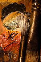 Painter's brushes rest on an oil pallet.