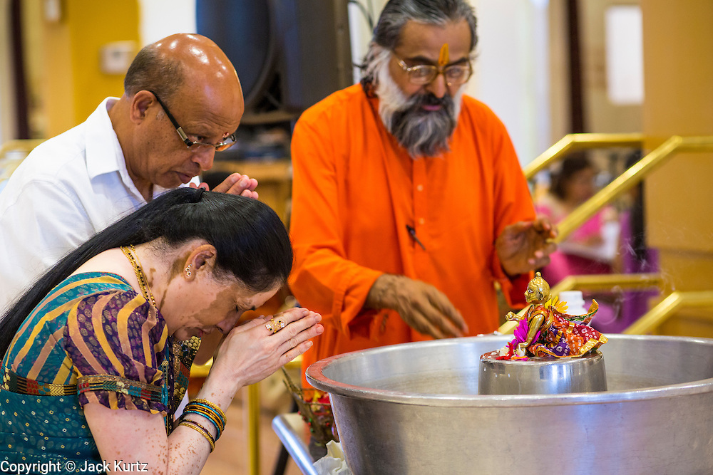 10 AUGUST 2012 - PHOENIX, AZ: A Hindu priest helps a couple make an offering to a diety during the celebration of Janmashtami at Ekta Mandir, a Hindu temple in central Phoenix. Janmashtami is the Hindu holy day that celebrates the birth of Lord Krishna. Hindu communities around the world celebrate the holy day. In Arizona, most of the Hindu temples in the Phoenix area have special celebrations of the day.    PHOTO BY JACK KURTZ
