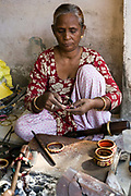 A woman making bespoke bangles in a shop in the Paharganj area, Jaipur, India