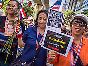 29 NOVEMBER 2013 - BANGKOK, THAILAND: Anti-government protestors march down Sukhumvit Road in Bangkok towards the US Embassy. Several thousand Thai anti-government protestors marched on the US Embassy in Bangkok. They blew whistles and asked the US to honor their efforts to unseat the elected government of Yingluck Shinawatra. The anti-government protestors marched through several parts of Bangkok Friday paralyzing traffic but no clashes were reported, even after a group protestors tried to occupy Army headquarters.         PHOTO BY JACK KURTZ    (NOTE GRAPHIC LANGUAGE IN SIGN)