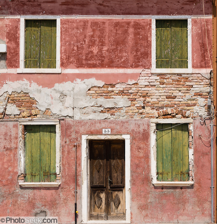 """Weathered red house with greenish yellow shutters. Burano, known for knitted lacework, fishing, and colorfully painted houses, is a small archipelago of four islands linked by bridges in the Venetian Lagoon, in the Veneto region of Italy, Europe. Burano's traditional house colors are strictly regulated by government. The Romans may have been first to settle Burano. Romantic Venice (Venezia), """"City of Canals,"""" stretches across 100+ small islands in the marshy Venetian Lagoon along the Adriatic Sea in northeast Italy, between the mouths of the Po and Piave Rivers. Venice and the Venetian Lagoon are honored on UNESCO's World Heritage List."""