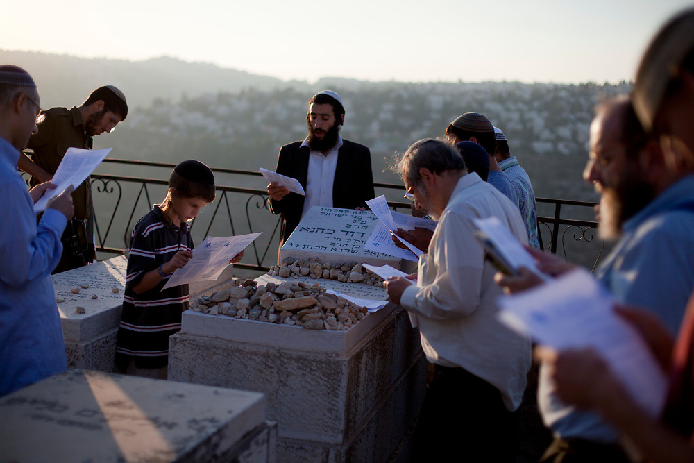 """Followers of the late Rabbi Meir Kahane, founder of both the Jewish Defense League (JDL) and """"Kach"""", an Israeli political party, pray at his grave at the Givat Shaul cemetery in Jerusalem on October 26, 2010, marking the 20th anniversary of his death after he was assassinated by an Arab gunman in a Manhattan hotel in November 1990."""