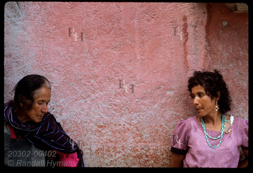 Older woman leans against pastel wall beside younger woman in late afternoon; Guanajuato, Gto. Mexico