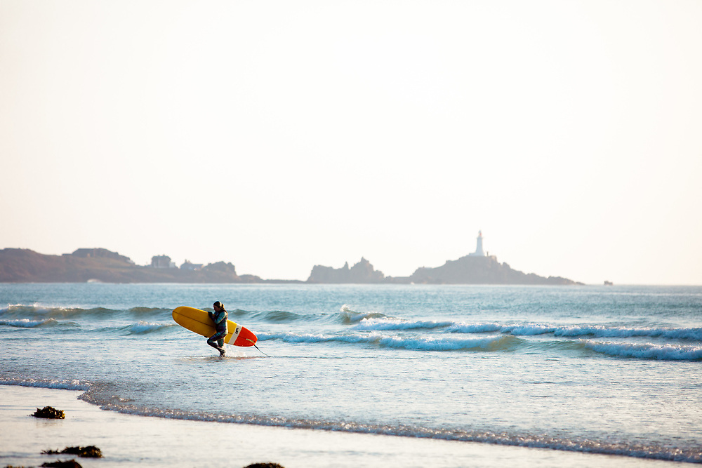 Surfer getting out of the water carrying her surf board at St Ouen's Bay, with views of the tourist attraction Corbiere lighthouse in the distance in Jersey, Channel Islands