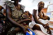 Kouadio Ahou Viviane (right) breast feeds her 16-month-old boy Emmanuel Ngora Kwame while they wait to see a doctor at the NDA health center in Dimbokro, Cote d'Ivoire on Friday June 19, 2009.