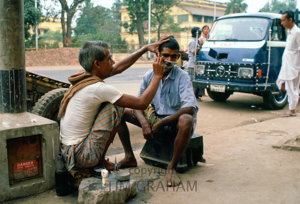 Street barber at work, Delhi, India