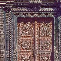 Intricate wood carvings adporna a door in Kathmandu, Nepal, 1986.