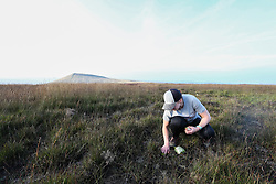 © Licensed to London News Pictures. 06/09/2021. Marsden, UK. National Trust volunteer Claire Goddard plants Sphagnum Moss on the Marsden Moor Estate in the South Pennines. Sphagnum Moss, a peat forming plant which helps to reduce flooding and reduce fire risk by acting as a sponge, is being planted to help restore large area of moorland which were devastated by fires in April 2021. Photo credit: Adam Vaughan/LNP