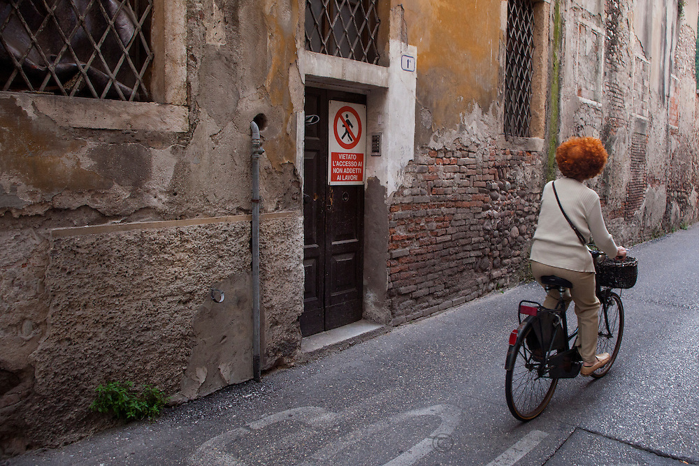 A woman riding a bicycle down a street in Verona, Italy.