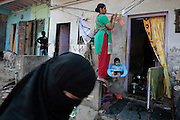 A woman hands her childs swing from a clothesline outside her home.  The slum of Cheetah Camp on the outskirts of Mumbai, India is a predominantly muslim community on living on the fringe while the city continues to grow.