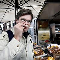 Nederland, Amsterdam , 7 april 2012..Noordermarkt.. Dick Veerman, oprichter van Foodlog ruikt aan een stukje Paasbrood bij een broodkraam tijdens de Boerenmarkt op zaterdag..Foto:Jean-Pierre Jans