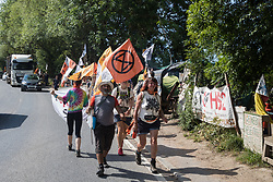 Harefield, UK. 26 June, 2020. Activists from HS2 Rebellion and Extinction Rebellion UK pass the Harvil Road protection camp as they take part in a 'Rebel Trail' hike along the route of the HS2 high-speed rail link. The activists, who departed from Birmingham on 20th June and will arrive outside Parliament in London on 27th June, are protesting against the environmental impact of the high-speed rail link and questioning the viability of the £100bn+ project.