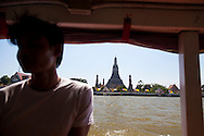 Traveling by boat down the Chao Phraya River through downtown Bangkok, Thailand,