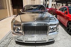 Silver Rolls-Royce luxury car parked  outside luxury hotel in Dubai United Arab Emirates