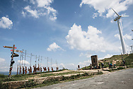 Pilgrims reach the summit at Alto del Perdón on the Camino de Santiago, located about 3.5 kilometers from Uterga, Spain. The summit is home to wind turbines as well as a wrought iron sculpture depicting pilgrims walking the Camino. (June 2, 2018)<br />