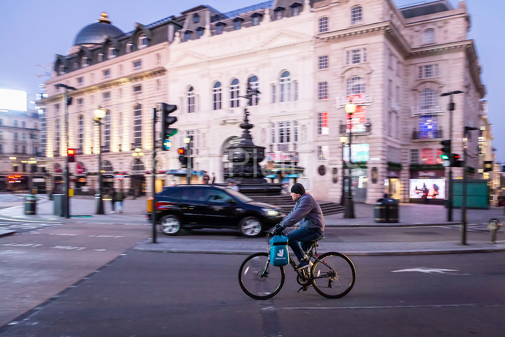A Deliveroo delivery rider cycles through an almost deserted Picadilly Circus in London on March 27th, 2020. The centre of London is extremely quiet with almost every business closed and very few people about because of the Governments lockdown measures due to the Coronavirus crisis. Gig economy workers ssuch as delivery riders and drivers are facing financial uncertainty caused by the economic shut down.