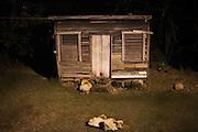 A man sleeps outside a wooden shack. Punta Gorda, Toledo, Belize. January 27, 2013.
